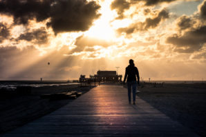 woman walking towards the sun