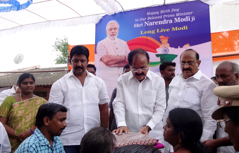 The Union Minister for Urban Development, Housing & Urban Poverty Alleviation and Information & Broadcasting, Mr. M. Venkaiah Naidu distributing the clothes marking the occasion of Prime Minister, Mr. Narendra Modi's birthday in Leprosy colony, at Kesarpally, in Gannavarm mandal, Krishna District of Andhra Pradesh on September 17, 2016.